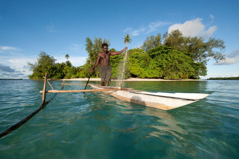 A Papua New Guinea islander paddles his dugout canoe to go fishing © Jürgen Freund / WWF