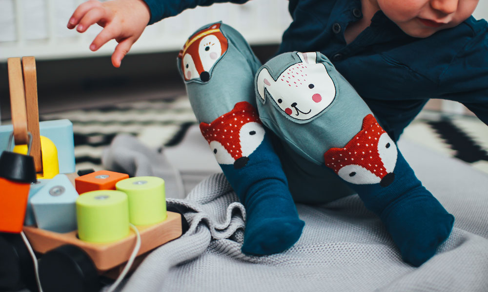 Baby playing with wooden toys. Photo by Daiga Ellaby on Unsplash