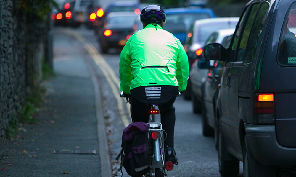 Cyclist commuting through a traffic jam, Ambleside, Cumbria, UK © Global Warming Images / WWF