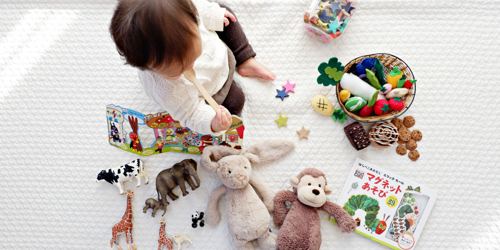 Baby with soft toys, books and wildlife toys. Photo by li tzuni on Unsplash