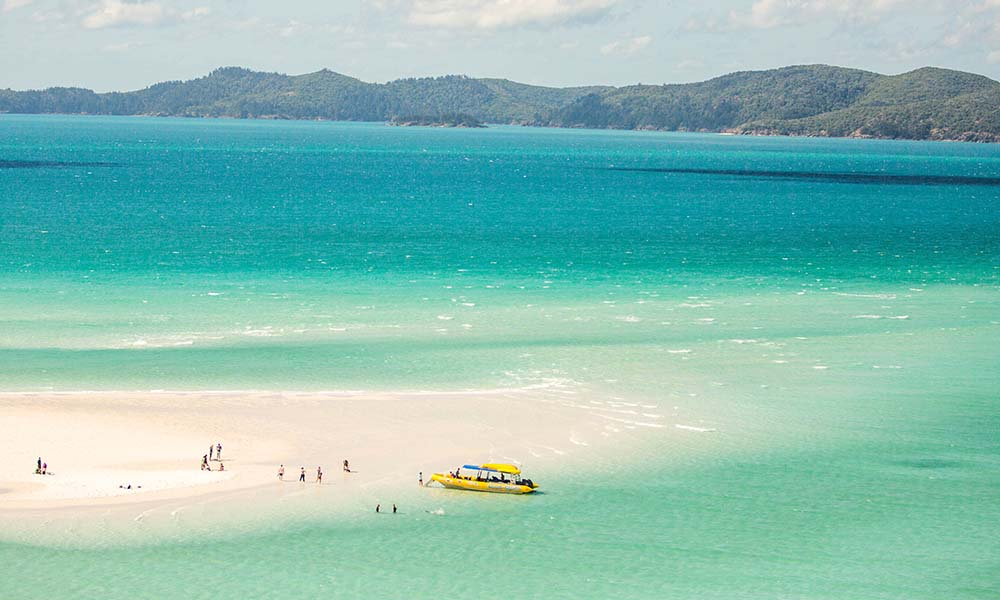 Tourists on Whitehaven Beach in the Whitsundays. Whitehaven Beach is 99% silica. Queensland, Australia © WWF / James Morgan