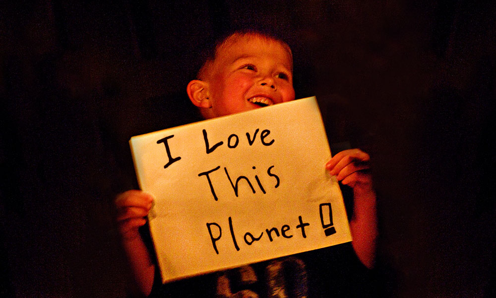 A young boy holding up a handmade sign reading I love this planet © Jeremiah Armstrong / WWF-Canada